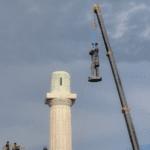 statue being taken off a pedestal with a crane
